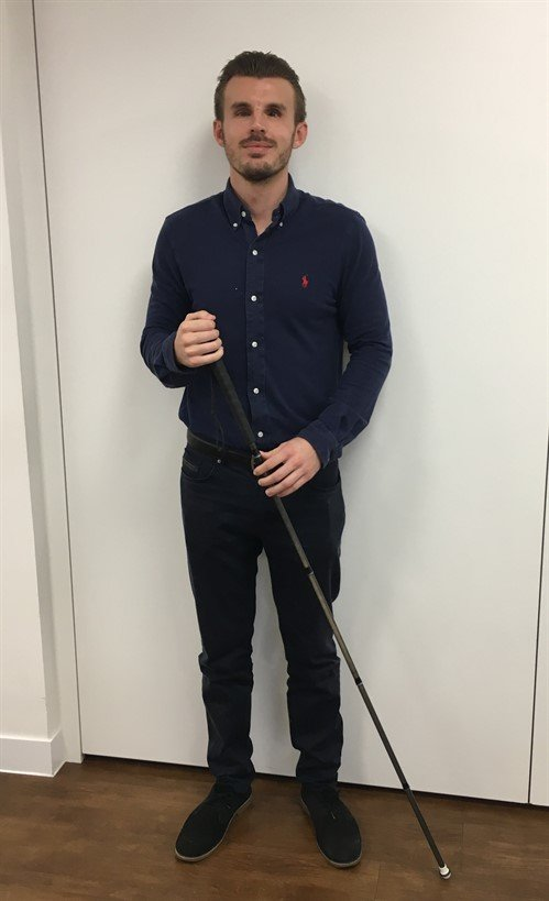 Image shows Alex Pepper standing holding his black mobility cane against a white background