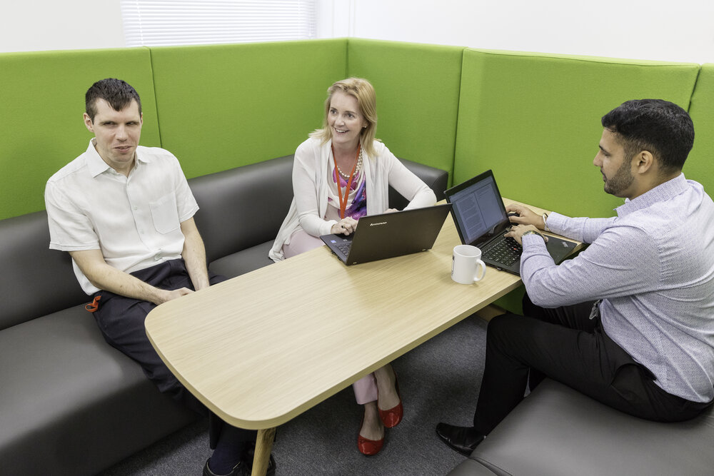 White man, white woman and Asian man sat around a table at laptops