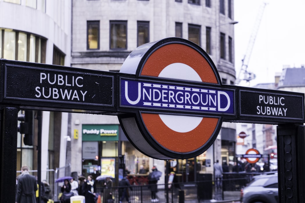 Public subway sign outside a tube station, with the London Underground roundel in the middle