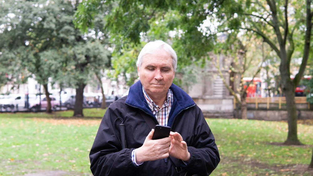 Elderly white man using his phone in the park