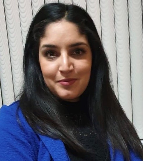 Renu Walia. South Asian woman with long black hair sat on a bed. She is wearing a blue blazer, black dress and black tights