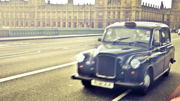 A Hackney carriage driving over Westminster Bridge, with Houses of Parliament in the background