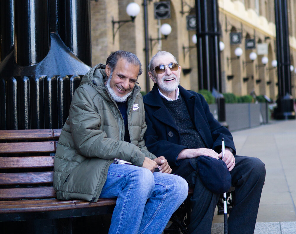 Asian elderly man to the left with grey hair and a white beard, sat next to a white man with white hair and beard and brown sunglasses. They are sat outside on a bench.