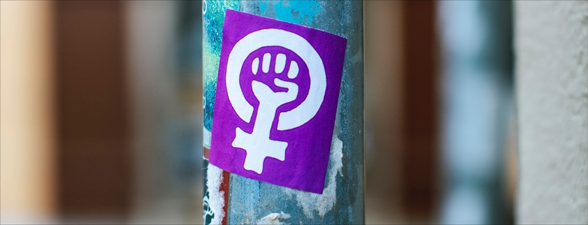 Close up a sign on a street pole. There is a purple sticker on the pole, with the feminist fist symbol in white.