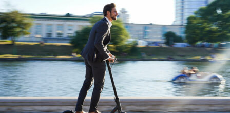 An image of a man riding an e-scooter alongside a waterway