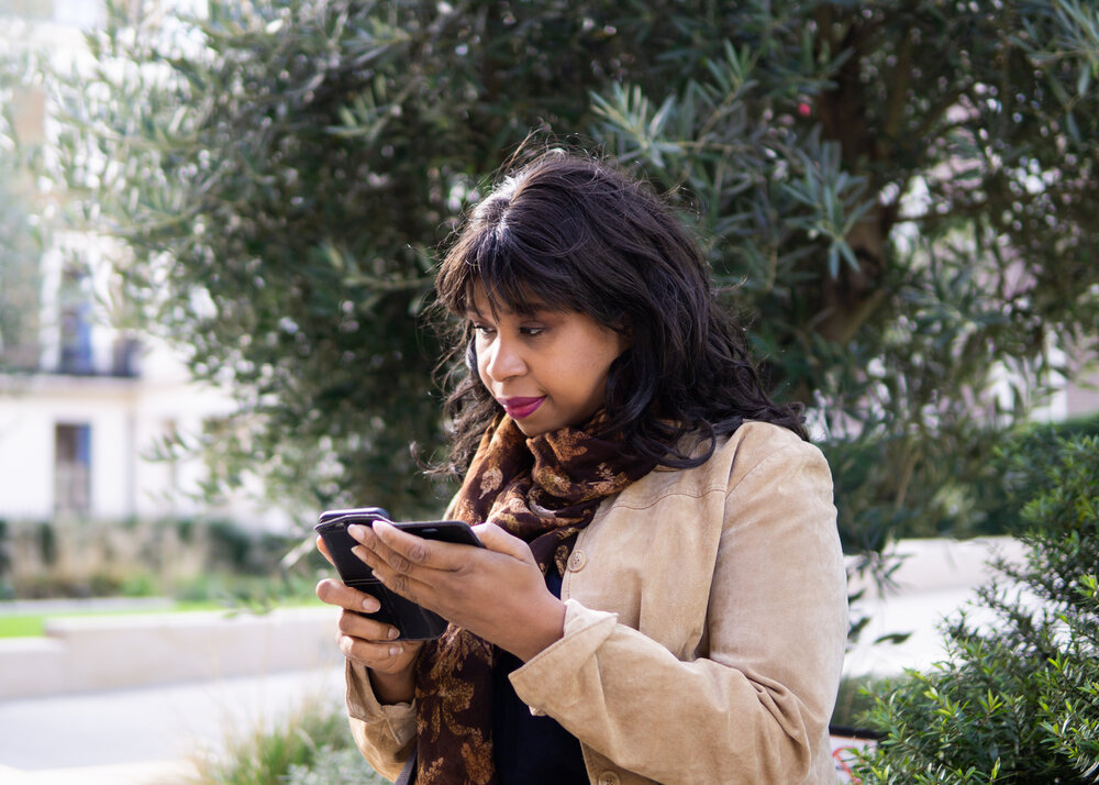Black woman with black hair and a tan coat, stood in front of a tree using her phone