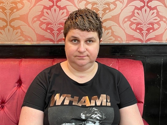 Charmaine, a white woman with short brown hair. She is sat on a red banquette seat. She is wearing a black 'WHAM' tshirt and she is looking at the camera.