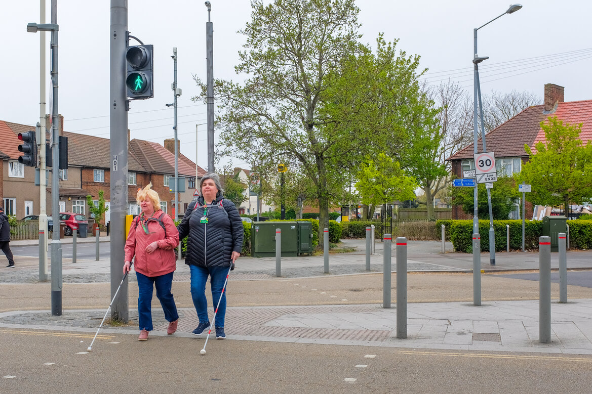 Two middle aged white women crossing a busy road at a controlled crossing. Both are holding mobility canes, the woman the right is using a red and white cane indicating hearing and sight impairment.