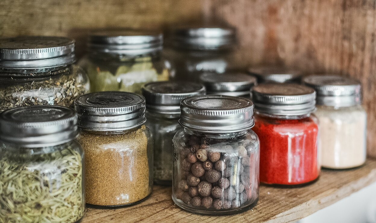 A variety of clear jars with spices in them on wooden shelf
