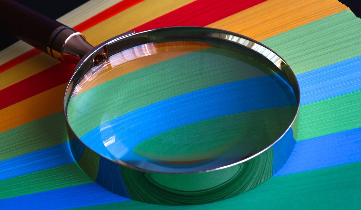 Magnifying glass placed on a piece of multicoloured paper