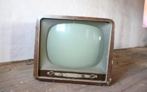 Very retro old tv, with brown casing and greenish rounded screen