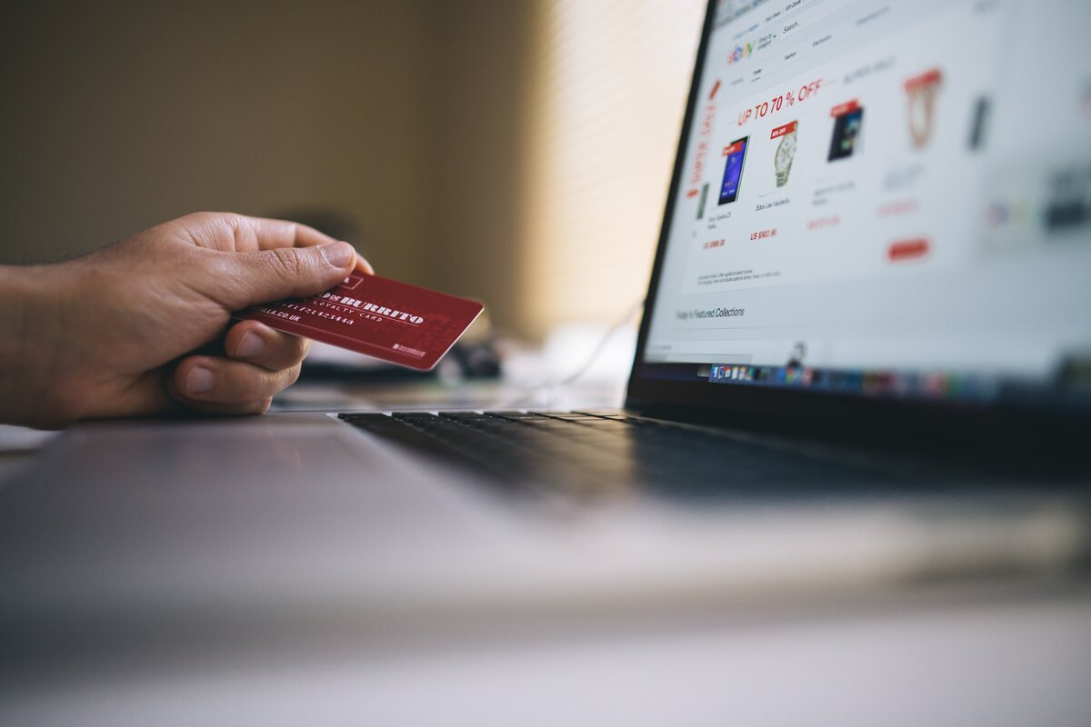 White person's hand holding a red credit card, by the black keyboard of a laptop computer. The laptop's browser is showing an online store.