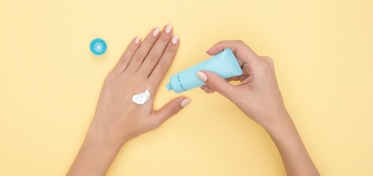 Hands of a white person, applying hand lotion out of a blue tube