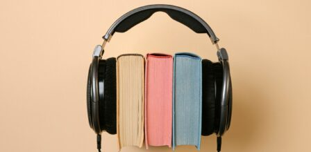 Three books, with beige, pink and blue pages, with a pair of over ear headphones holding them together