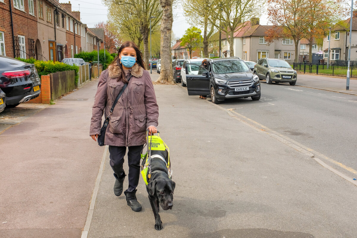 Bhavini Makwana, a South Asian British woman walking on a footpath towards the camera. She is being guided by her black Labrador guide dog. She is walking along a residential street, and there are cars lining the road behind her.