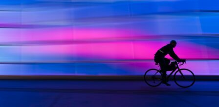 Blue and pink background, with a cyclist speeding from left to right.