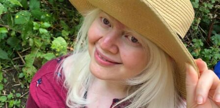 Eshita, wearing a beige wide brimmed hat and a magenta top. Eshita is touching the brim of her hat. She has very light coloured hair and a pair of sunglasses resting in the neck of her shirt.