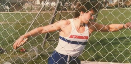 Jonathan Ward, training for the Paralympics. He is inside a discus circle and cage, preparing to throw the discus. The photo is from the 80s or early 90s. Jonathan is wearing blue trousers and a white tank top.