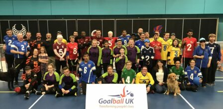 Lots of Goalball players on court, with a Goalball UK sign in front of them