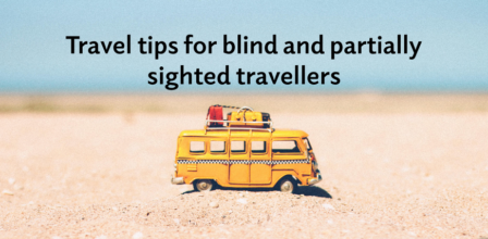 """""""Travel tips for blind and partially sighted travellers"""". A yellow toy camper van with luggage loaded on top on a small mound of sand."""