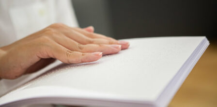 White hand reading braille on sheets of paper.